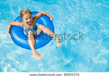 Swimming - little girl playing in blue water - space for text