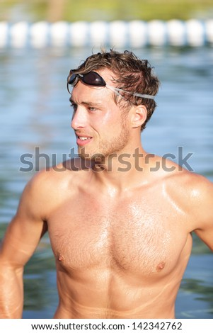 Swimming man portrait - handsome male swimmer in outdoors pool wearing swimming glasses. Good-looking young man fitness sports model relaxing after workout for triathlon.