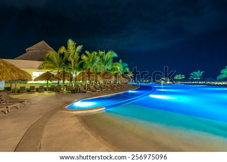 Swimming pool and a grass beach umbrellas with lounges at night, dawn time. Mexico.