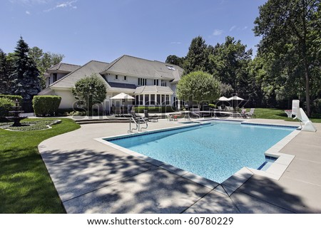 Swimming pool and deck in back of luxury home - stock photo