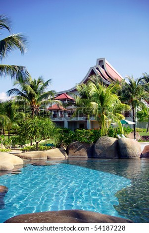 Swimming pool and houses of tropical resort.