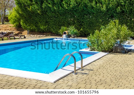 Swimming pool and lush vegetation - stock photo