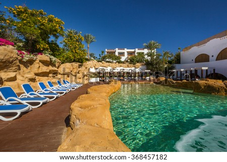 Swimming pool and luxury buildings behind it, palm trees, loungers  - stock photo