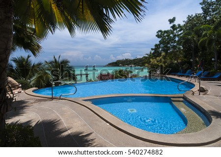 Swimming pool and palm trees near the tropical beach