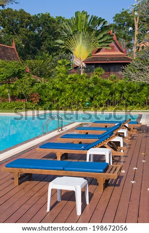 Swimming pool and sun beds in tropical garden , Thailand