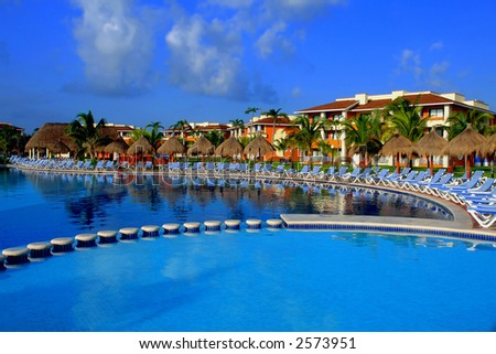 swimming pool area in tropical resort with long chairs around the pool