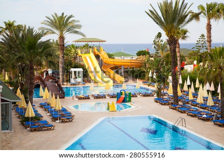 Swimming pool area, sun beds, palms and the sea at the back - stock photo