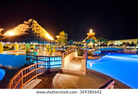 Swimming pool at a luxury caribbean, mexican resort at night, dawn time. - stock photo