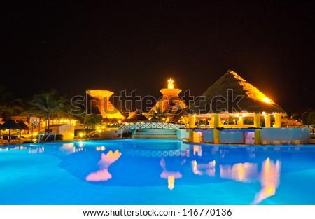Swimming pool at a luxury caribbean resort at night, dawn time. Bahia Principe, Riviera Maya, Mexican Resort. - stock photo