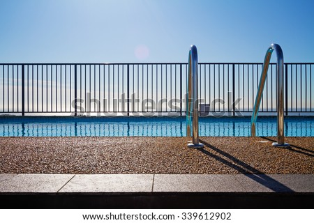 Swimming pool edge with ladder, fence and sky background - stock photo