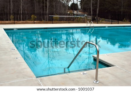 Swimming pool entry steps and hand rail - stock photo