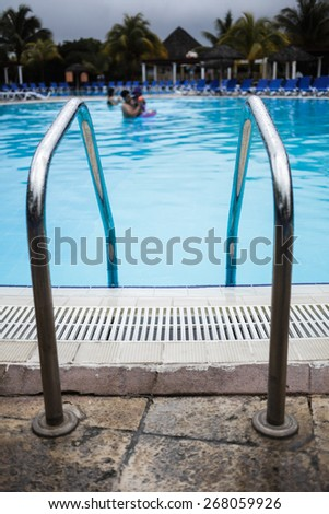 Swimming Pool Ladder Close-up with blurry people in background - stock photo