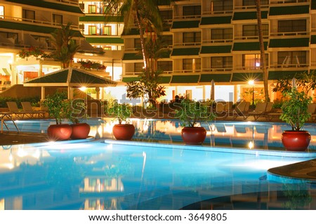Swimming pool, night, hotel and palm trees