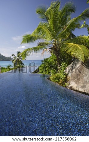 Swimming pool of the Banyan Tree Hotel with ocean in background, Anse Intendance, Mahe', Seychelles - stock photo