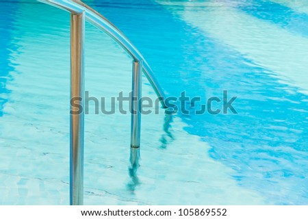 Swimming pool Stairs with hand-rails on water background - stock photo