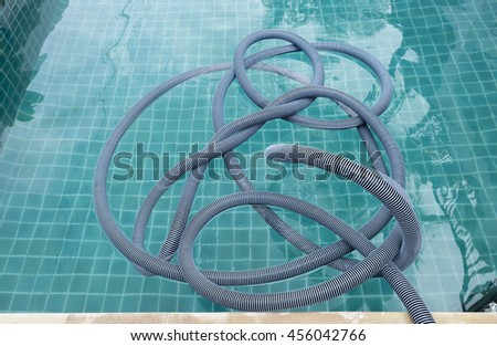 Swimming pool vacuum hose floating in the pool after cleaning in summer  - stock photo