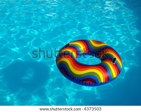 Swimming pool with a brightly coloured inflatable ring. - stock photo