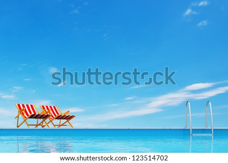 Swimming pool with beach chairs - stock photo