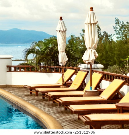 swimming pool with beds overlooking the sea and mountains - stock photo
