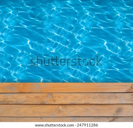 Swimming pool with blue clear water and wooden deck - stock photo