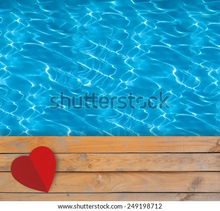 Swimming pool with blue clear water, wooden deck and red paper heart - stock photo