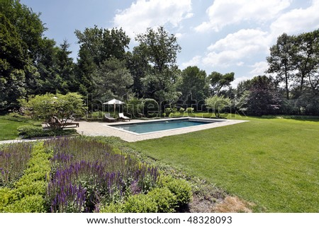 Swimming pool with brick deck and flowers - stock photo