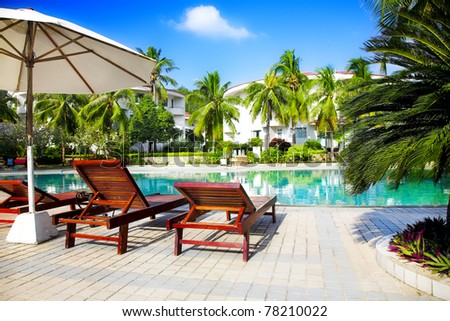 swimming pool with coconut tree and white umbrella - stock photo