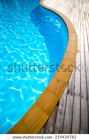 Swimming pool with concrete and wooden deck as a background , blue swimming pool with wood flooring stripes summer vacation - stock photo