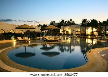swimming pool with evening illumination in tropical resort - stock photo
