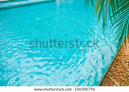 swimming pool with mosaic tiles and still water with the pool edge showing across a corner.