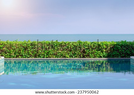 Swimming Pool with Ocean and Sunlight in background - stock photo