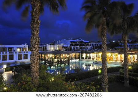swimming pool with open-air restaurant in night illumination at the modern luxury hotel, Crete, Greece - stock photo