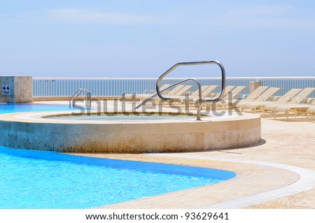 Swimming pool with outdoor jacuzzi. - stock photo