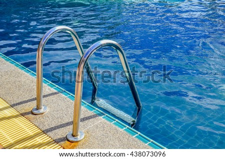 Swimming pool with stair and blue relaxing water - stock photo