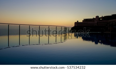 Swimming pool with stair and Panoramic dramatic tropical sunset on the sea