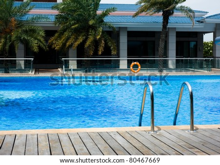 Swimming pool with stair at hotel close up. - stock photo