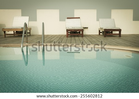 swimming pool with steel ladder in resort - stock photo