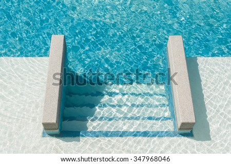 Swimming pool with steps down to the pool - stock photo