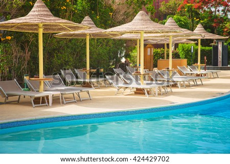 swimming pool with sun loungers and parasols - stock photo