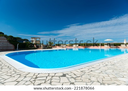 swimming pool with tiled border and  turquois water at blue sky - stock photo