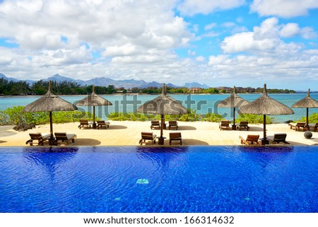 Swimming pool with umbrellas on tropical beach in Mauritius - stock photo