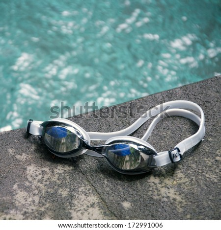Swimming sport goggles on the poolside - stock photo