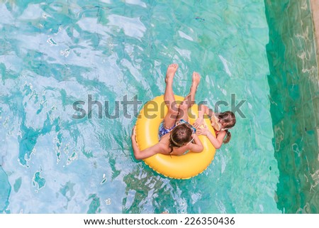 Swimming, summer vacation - lovely child boy and girl playing in blue water (space for text) - stock photo