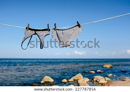 Swimsuit hanging on a rope on the sea beach - stock photo