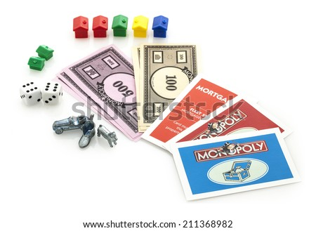 SWINDON, UK - JUNE 11, 2014: English Edition of Monopoly showing Money, Cards, Houses, Dice and Markers,  The classic trading game from Parker Brothers was first introduced to America in 1935.  - stock photo