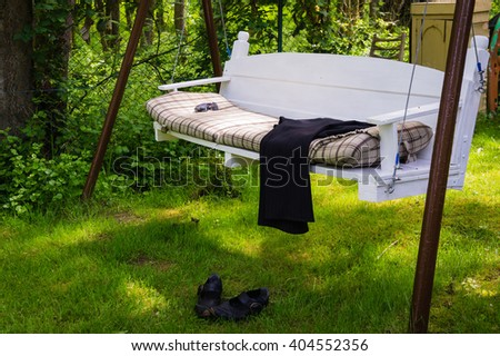 Swing bench  in a lush garden with woodland backdrop for relaxing on hot summer days - stock photo