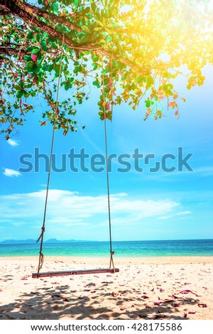 Swing hang from coconut tree over beach. Vacation concept - stock photo