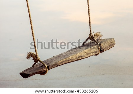 Swing hanged on a tree ,Wooden swing in the garden,wooden swing with green grass background in the park,empty swing - stock photo