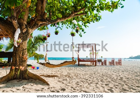 Swing hanging under a big tree for wedding ceremony decoration with pavilion and wedding arch on the beach - stock photo