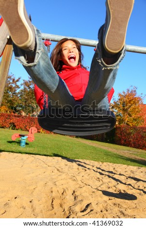 Swing. Happy young woman swinging on a playground. - stock photo
